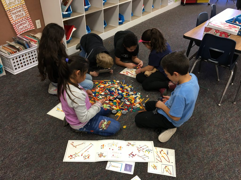 Four girls and two boys making things out of building blocks.